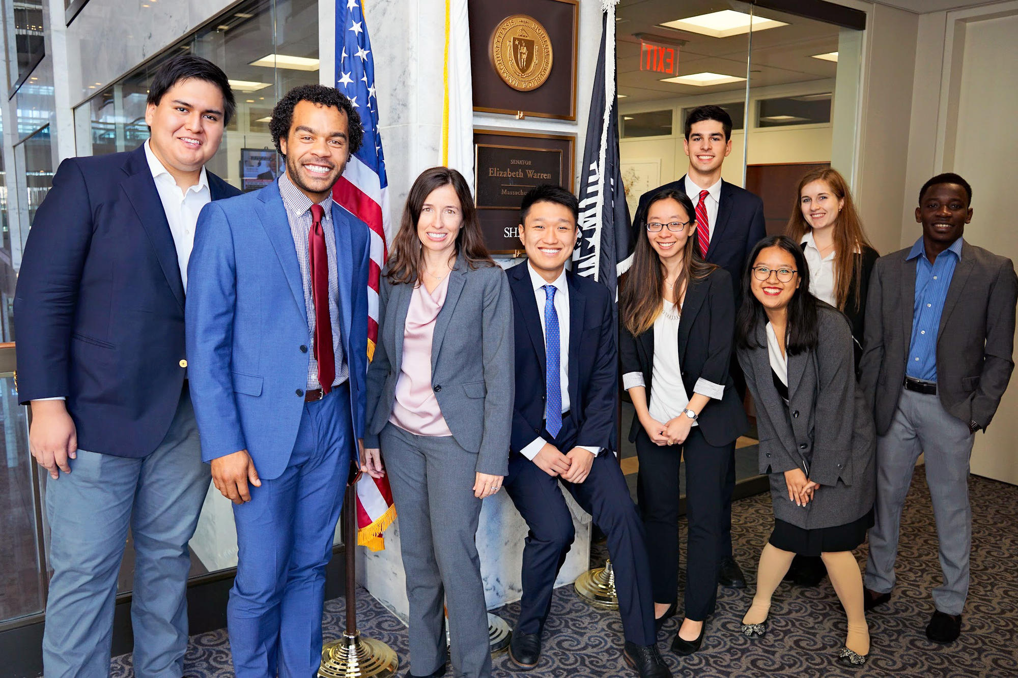 Nine members of the advocacy trip pose in front of the plaque outside Senator Warren's office. They wear dark suits for their meetings on Capitol Hill.