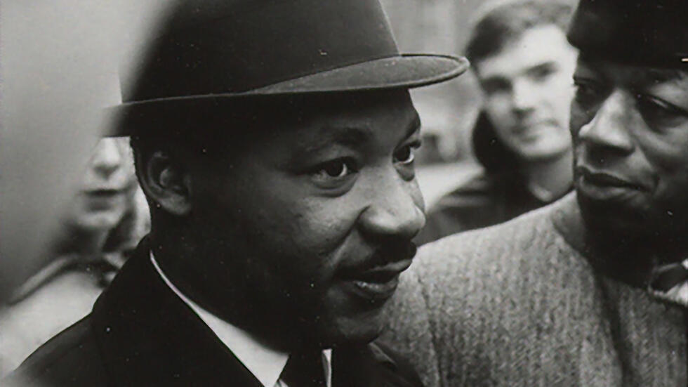Martin Luther King Jr in a black hat and suit, peering off camera surrounded by people