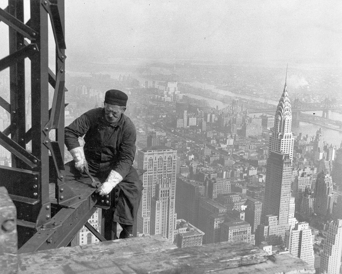 Black and white photo of construction worker on scaffolding on high building in NYC.