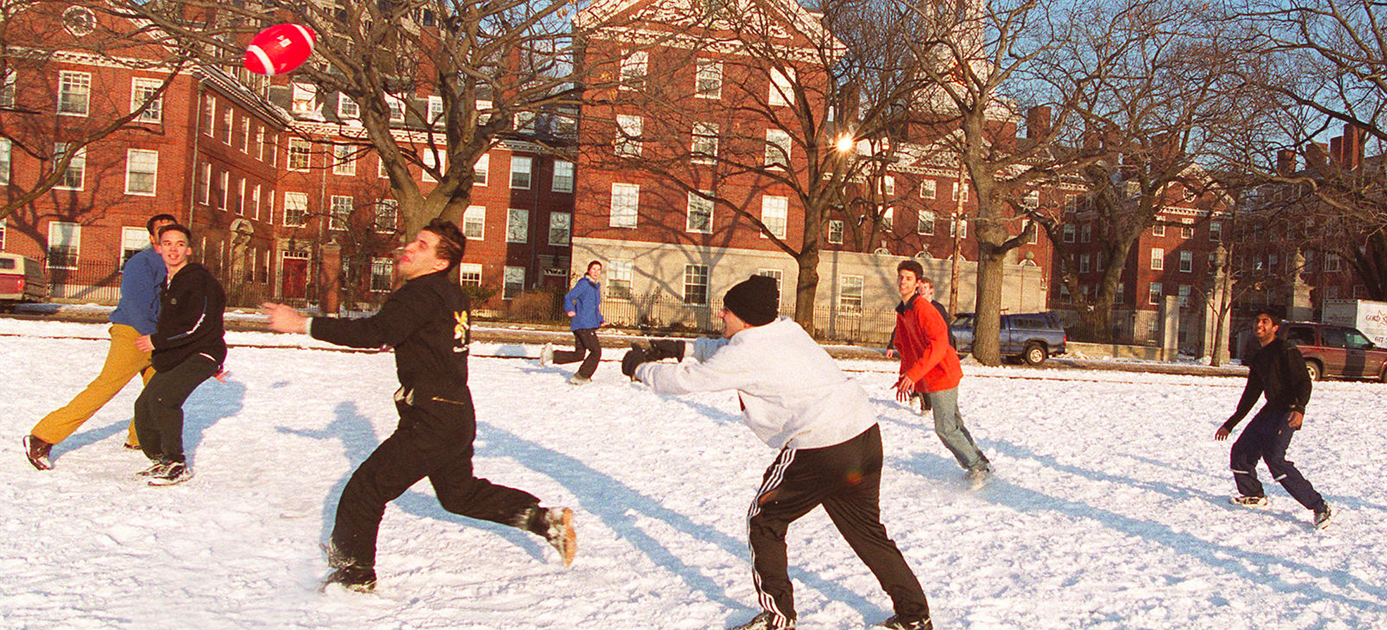 students playing football in the snow