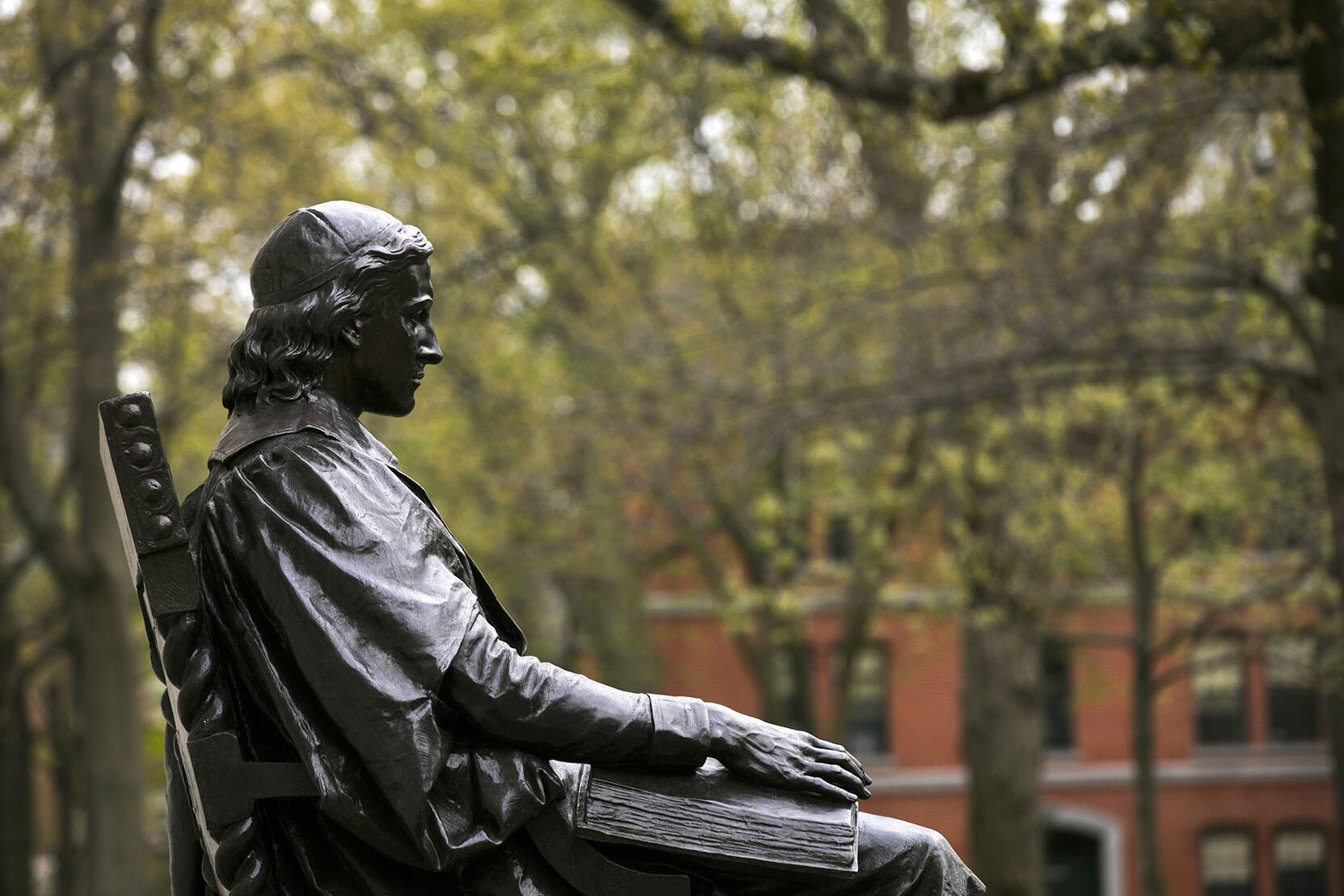 John Harvard statue with spring foliage in the background