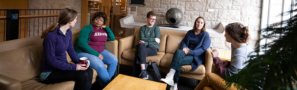 Students sitting in a lounge area outside the library entrance