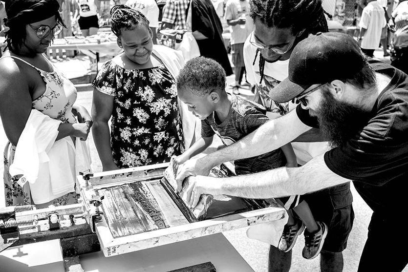Rev. Erik and artists at The Sanctuaries help residents screenprint wearable protest art