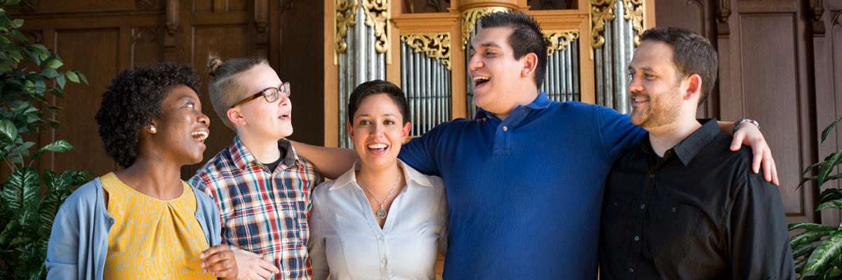 Five young adults smiling in a religious space in front of a pipe organ. The young people are of various races and genders.