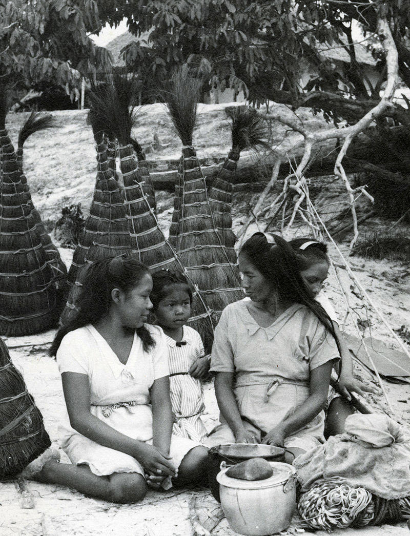 [Family] seated with large L. piassaba bundles.  Rio Negro, Columbia.