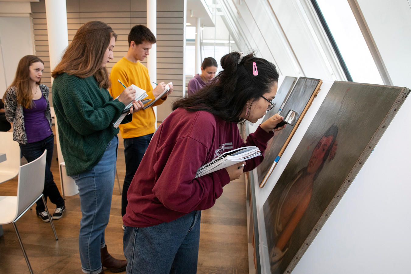 Emerald Mae GoingSnake (left) and four fellow students examine oil portraits of Native American leaders painted in the early 1800s.
