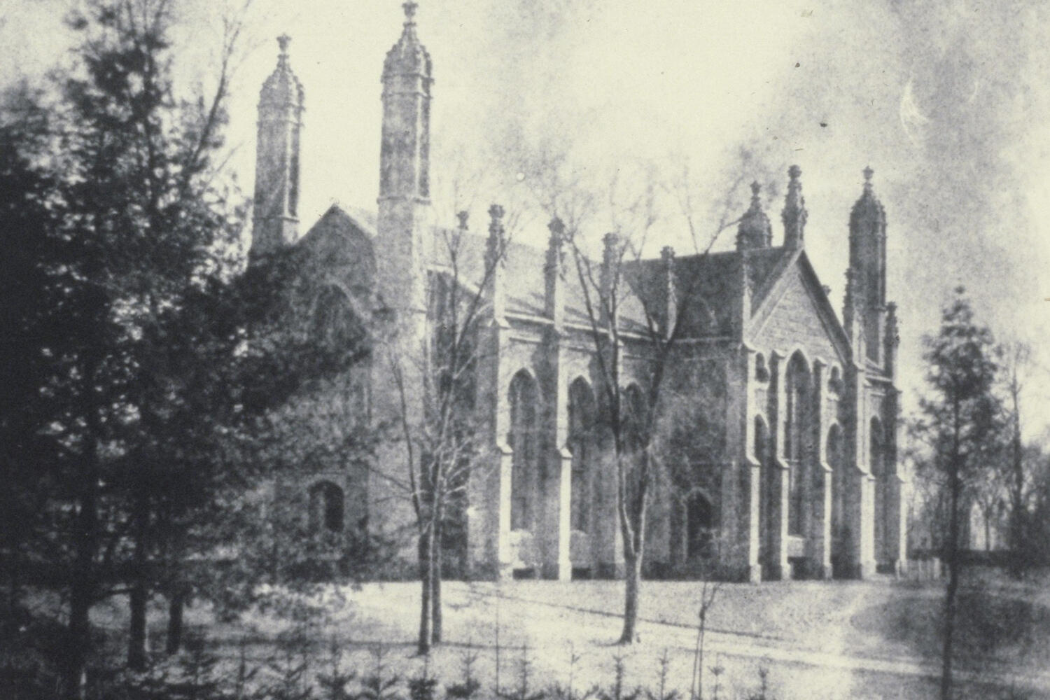 A black-and-white early photograph of Gore Hall, a large Gothic structure with four corner turrets, with trees in the foreground.