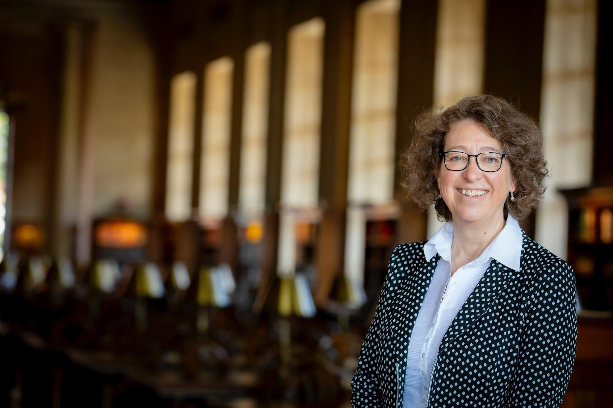 Portrait of Martha Whitehead wearing glasses, a black polka-dotted jacket, and white collared shirt, standing in the Loker Reading Room, with study tables and lamps in the background.