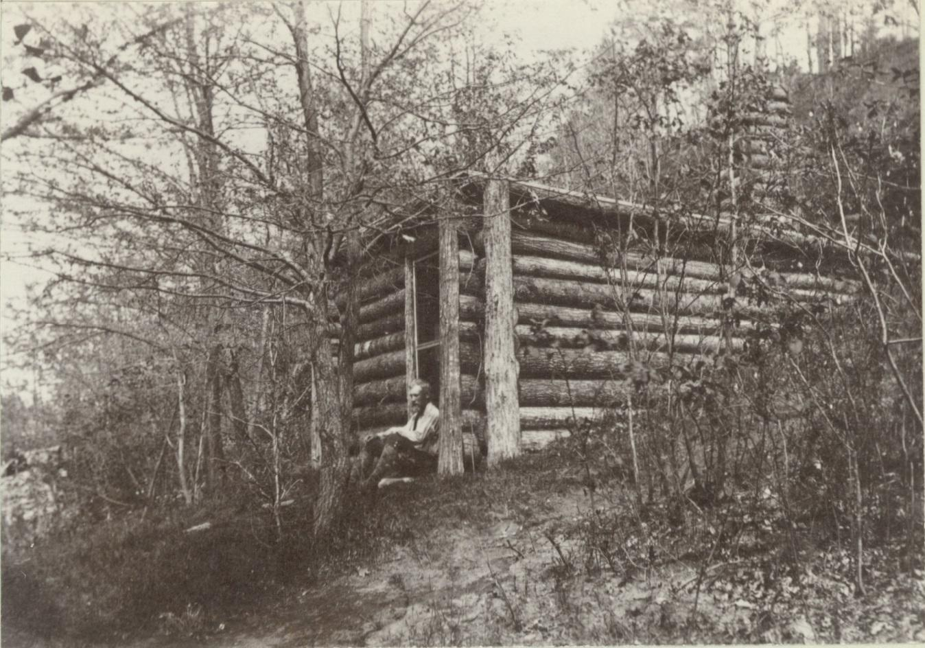 Brewster seated in front of cabin.