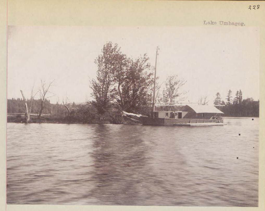 Black and white photograph of a small house boat on a lake with a person standing on deck.