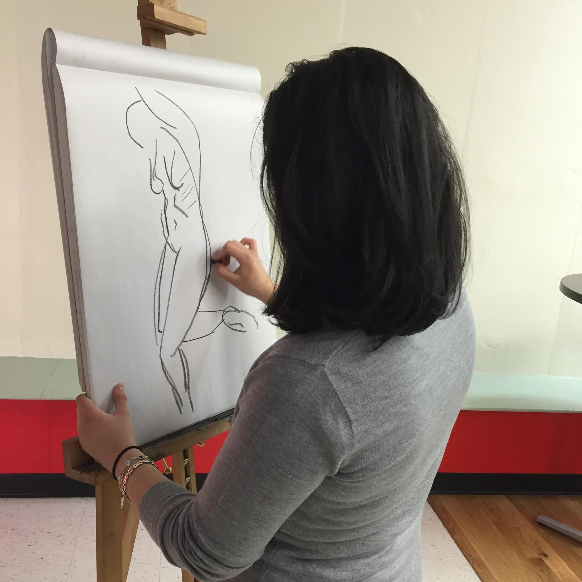 Student at easel sketching a figure