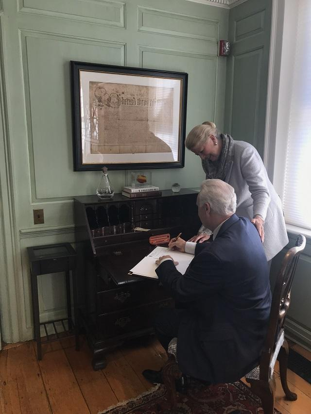 President Ricciardone signs the agreement while Margot Gill looks on
