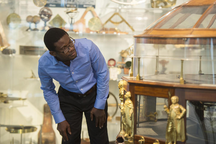 Man looking at a scientific instrument in a gallery.