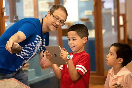 Male Museum staff member showing two young boys a museum object through an iPad.