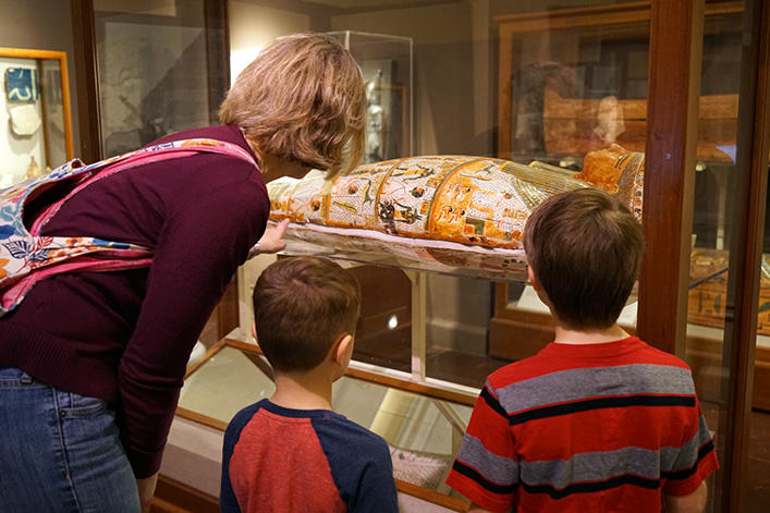 A woman with two kids looking at a mummy.