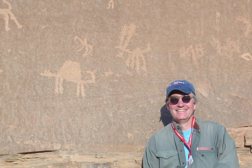 Harvard Museum of the Ancient Near East's Deputy Director and Curator, Joseph Greene, sitting in front of an archaeological site with markings.