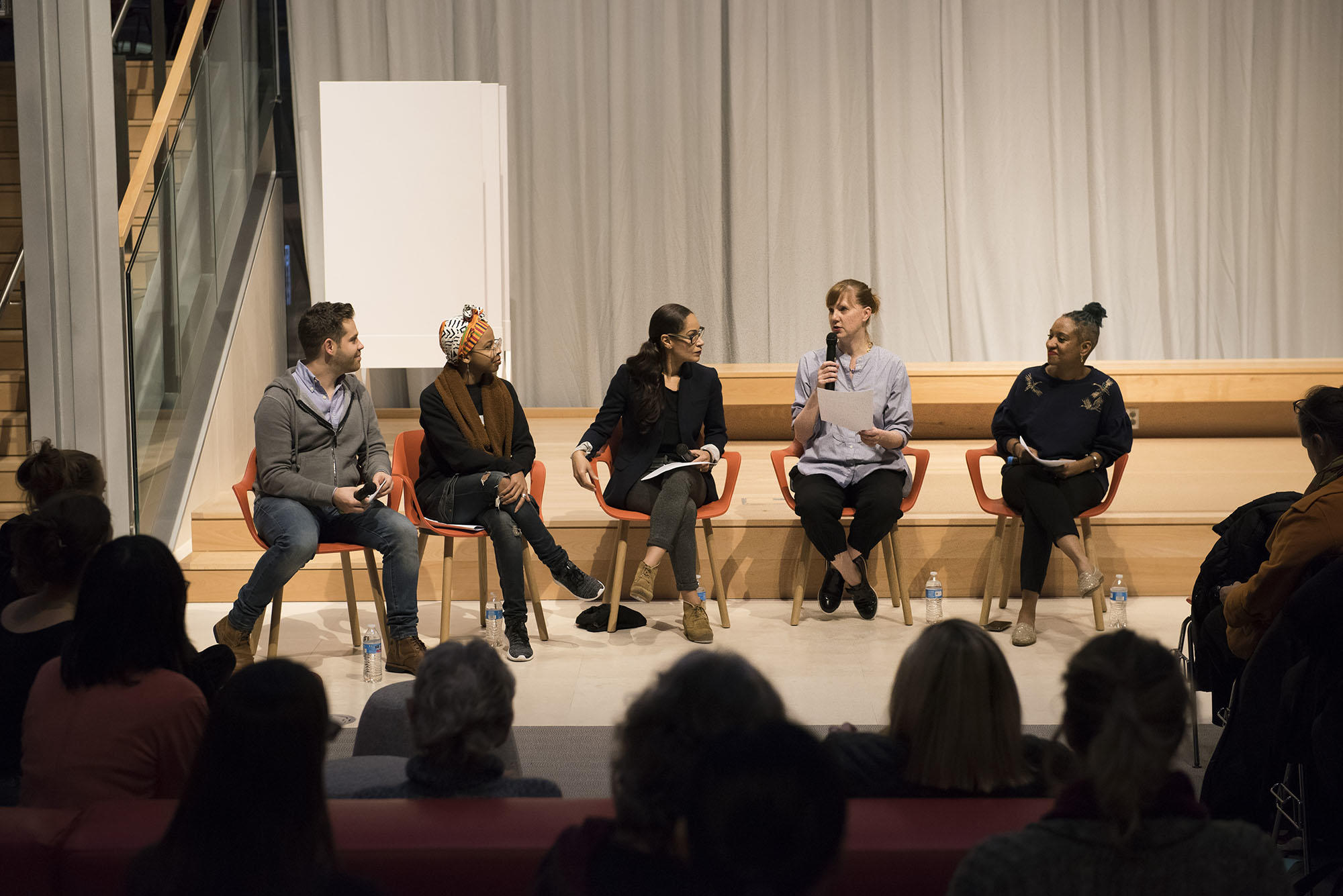 Five diverse panelists sit in a half circle on a stage with microphones in front of a full audience.