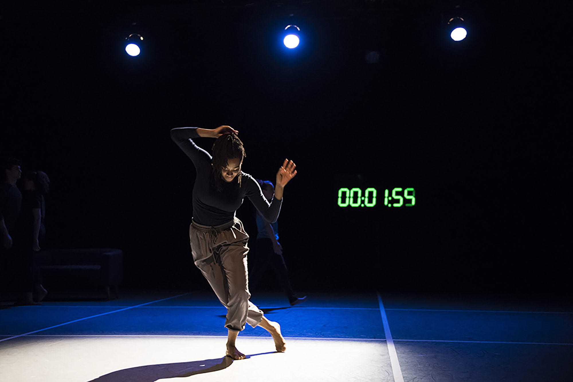 Harvard Dance Project student in movement on stage with dramatic lighting and time clock in the background.