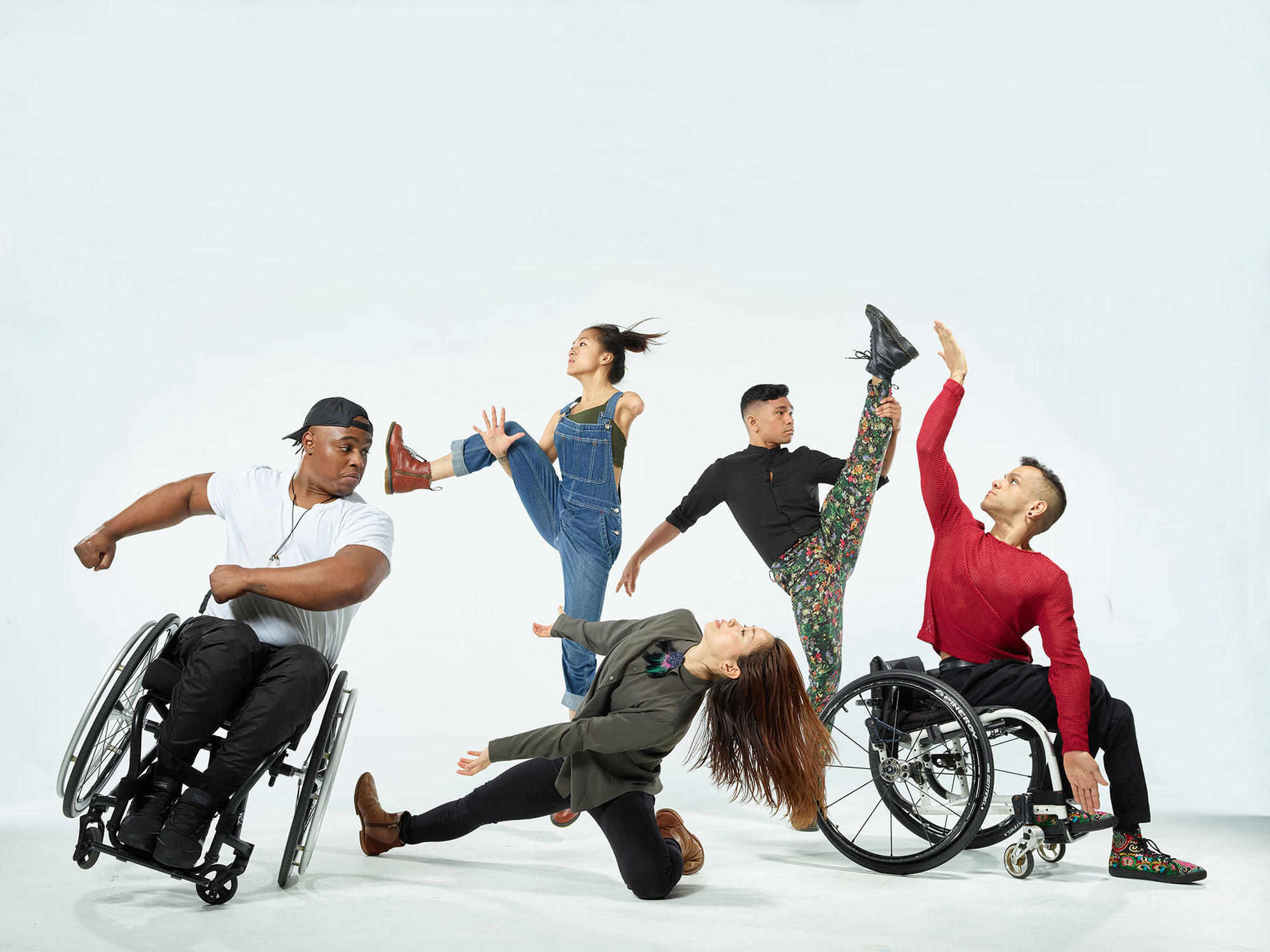 Five physically diverse dancers in motion; two of the dancers are in wheelchairs.