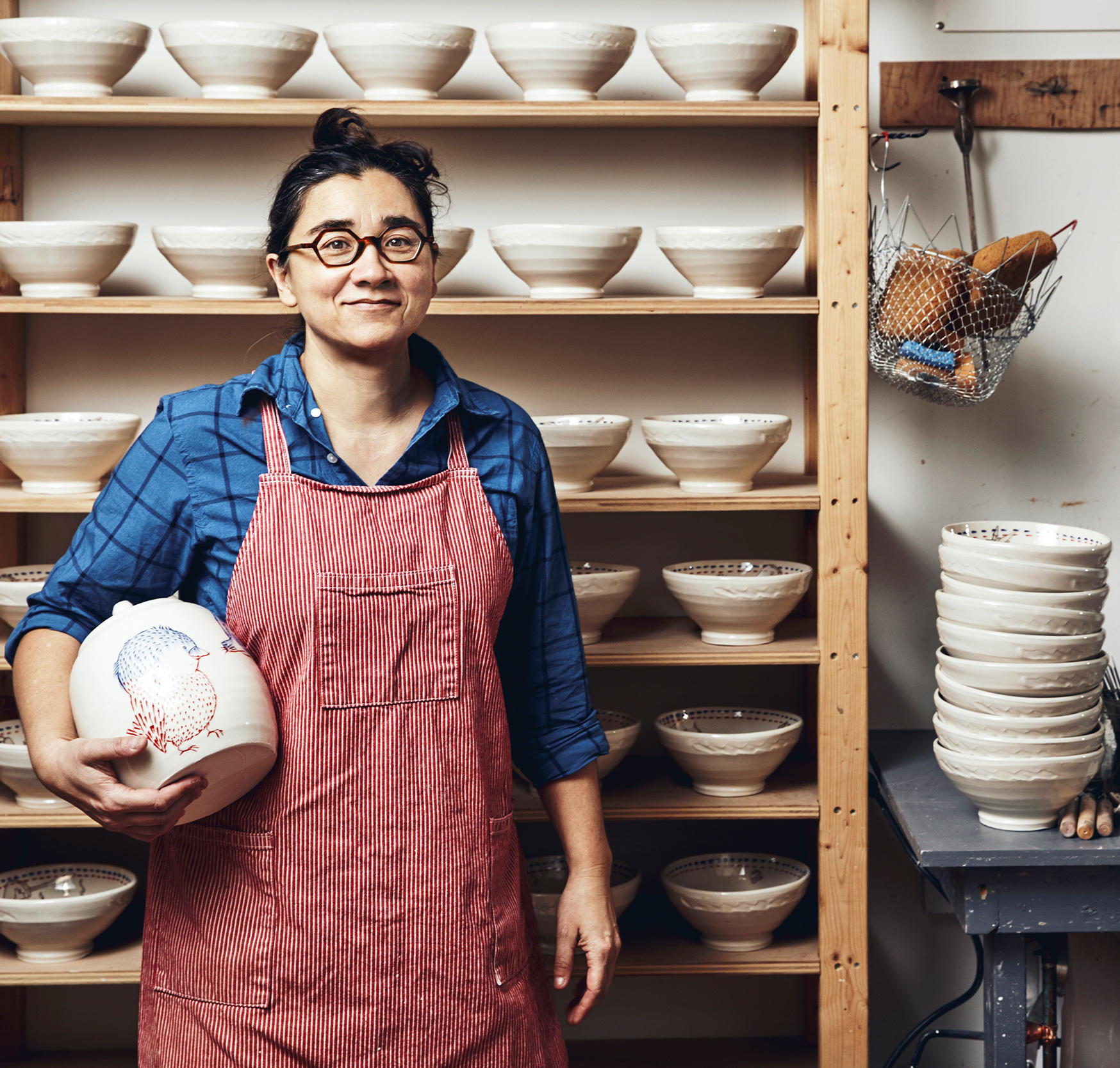 photo of a potter standing in front of a rack of ramen bowls holding a jar.