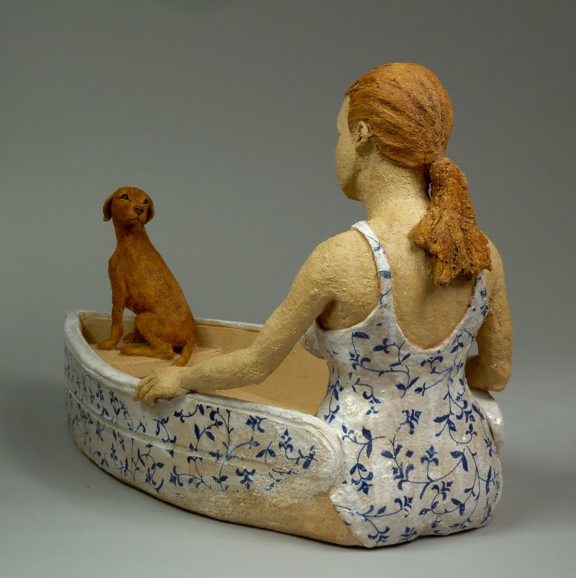 ceramic sculpture of a woman sitting in a rowboat