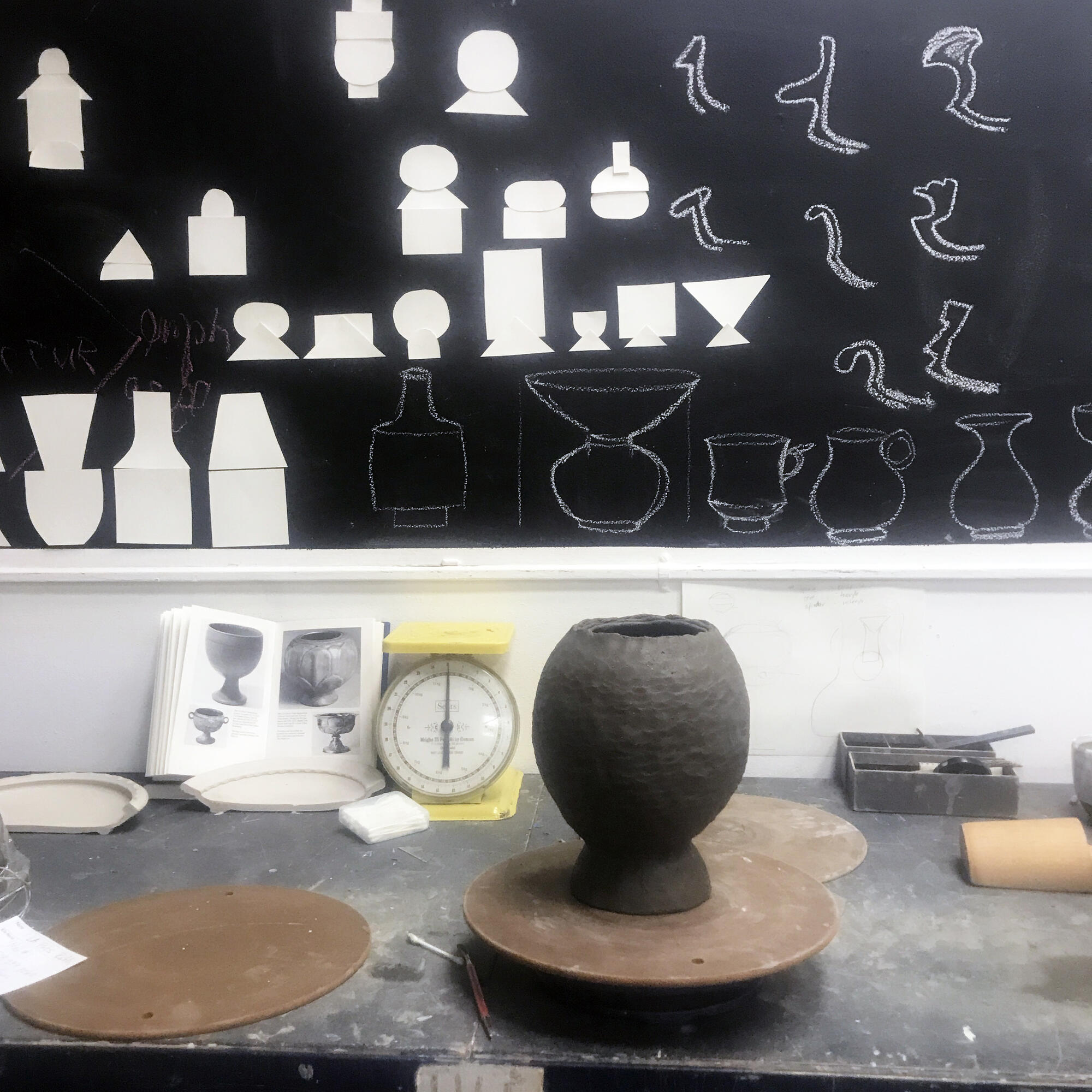 Design on chalkboard, vessel in progress on table by Ruth Easterbrook