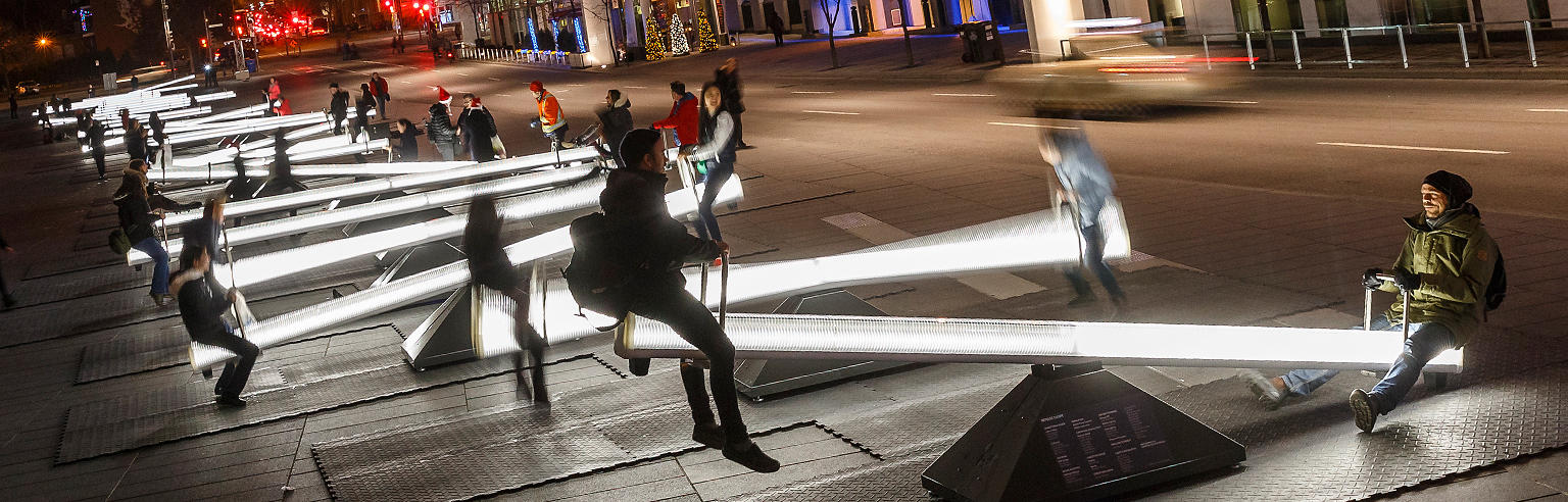 mpulse, an interactive public art experience of light and sound, consisting of a series of acoustic, illuminated see-saws that create waves of light intensification and sound sequences when activated by the public.