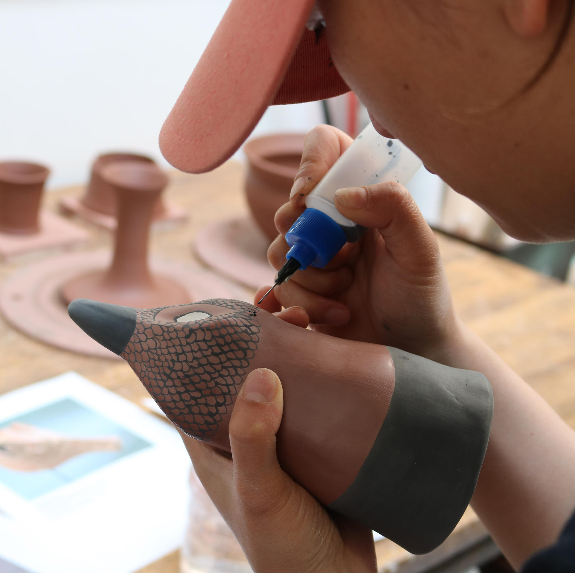 Person decorating an clay object shaped like an eagle's head