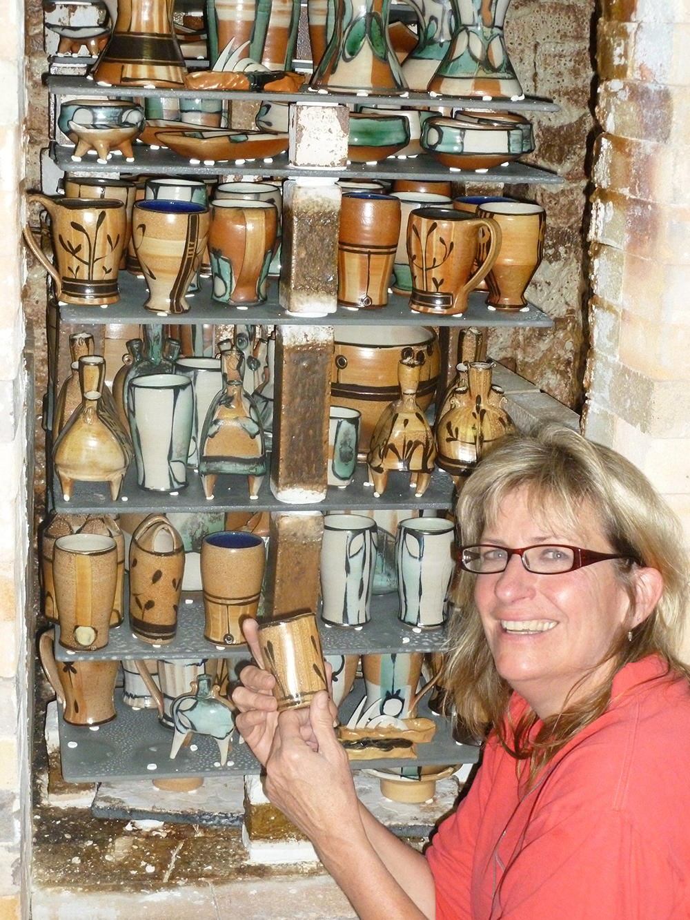 Suze Lindsay, potter, smiling in front of salt kiln.