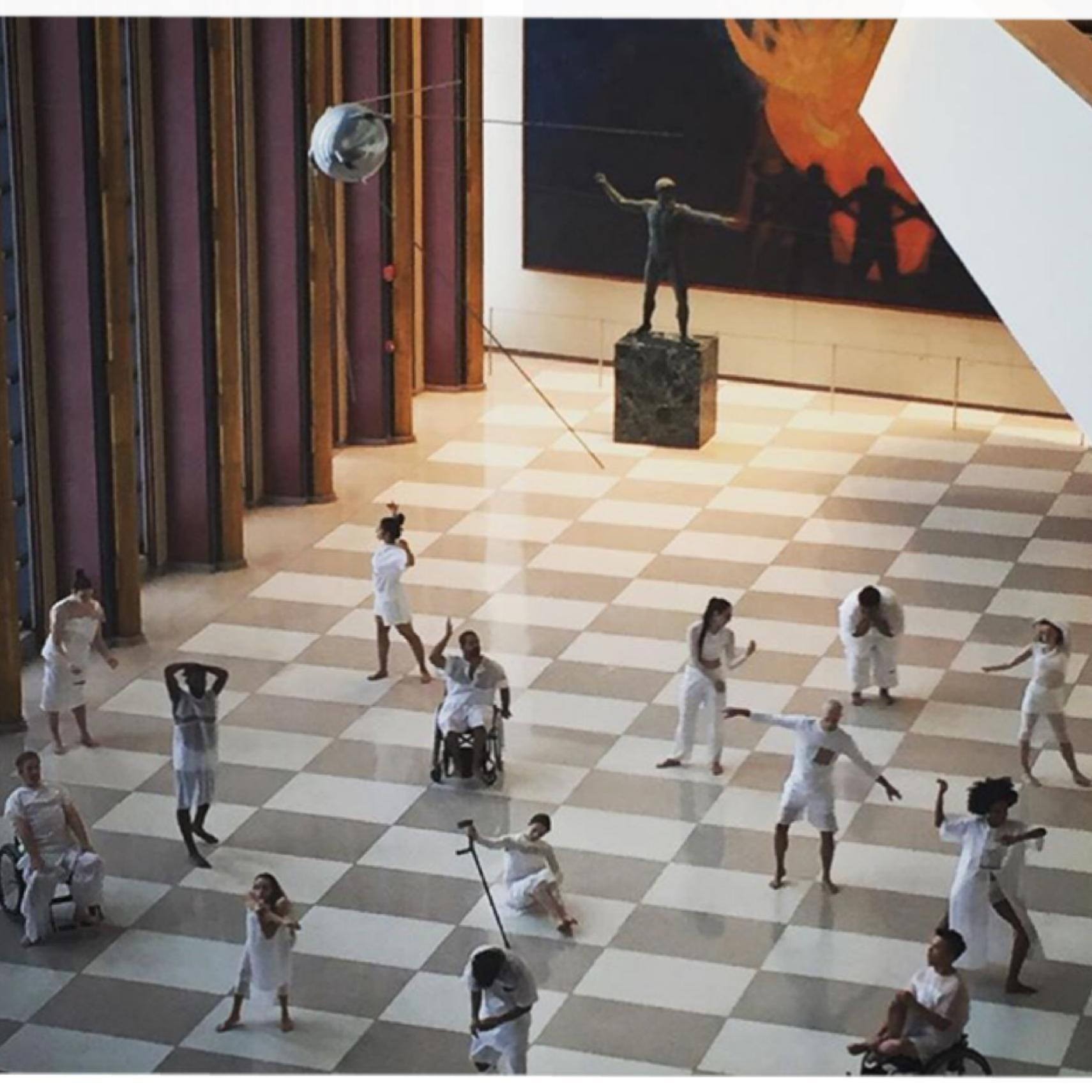 Dancers pose in different positions like in a sculpture garden. Some are in wheelchairs, some are standing, one poses on the ground with a propped up cane. Dancers are dressed in all white and they are in a big open room in UN headquarters.