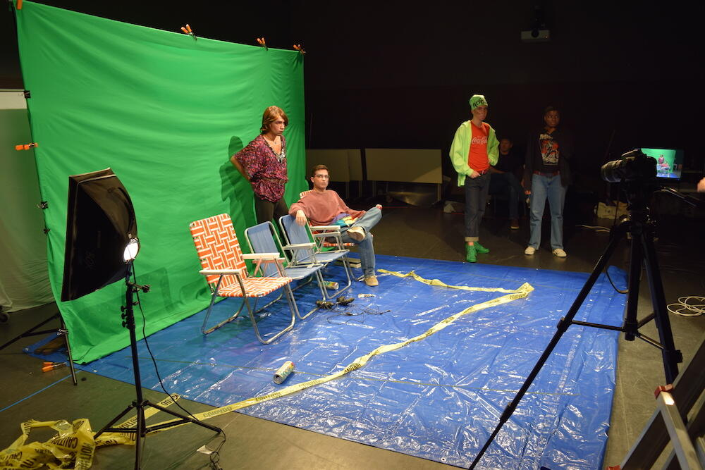 Four students working with a camera and a greenscreen.
