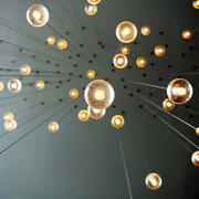 A photo of hanging, lit lightbulbs taken from below