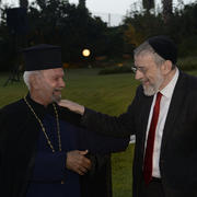 Muslim and Jewish man shake hands and smile