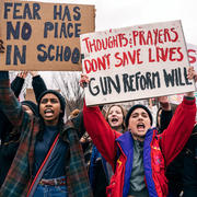 "Students hold signs, ""Thoughts and Prayers Don't Save Lives, Gun Reform Will"""