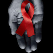 AIDS ribbon in a hand