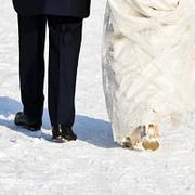 Man in suit and woman in wedding dress walk through snow, with backs to the camera