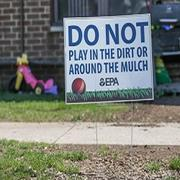 "In foreground, a sign posted on a lawn reads ""Do not play in the dirt or around the mulch - EPA."" In background is a child's pink three-wheeled riding toy."
