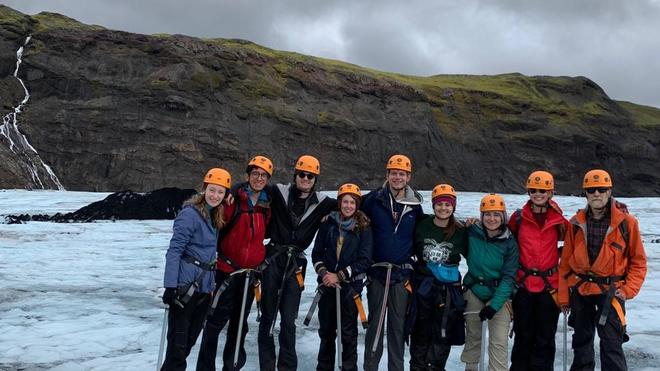 Photo of EPS students, with pickaxes and orange helmets, standing on icy ground in front of cliffs in Iceland