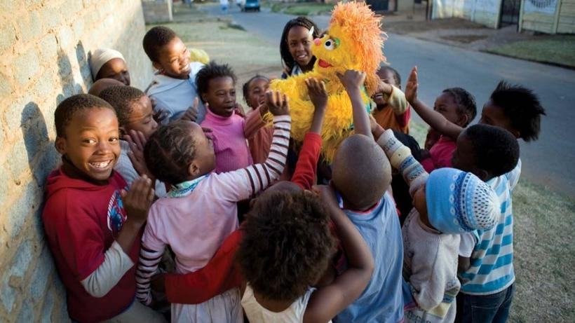 South African children play with Kami, a furry yellow five-year-old HIV-positive girl muppet orphaned by AIDS. ©2007 Sesame Workshop. All Rights Reserved. Photographed by Ryan Heffernan.