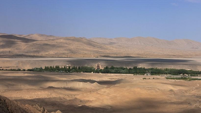 The cave temples of Mogao, carved into the cliff face along the Daquan River, are shaded by poplar trees planted in the twentieth century and surrounded by austere desert. The nine-story temple can be seen at the center.
