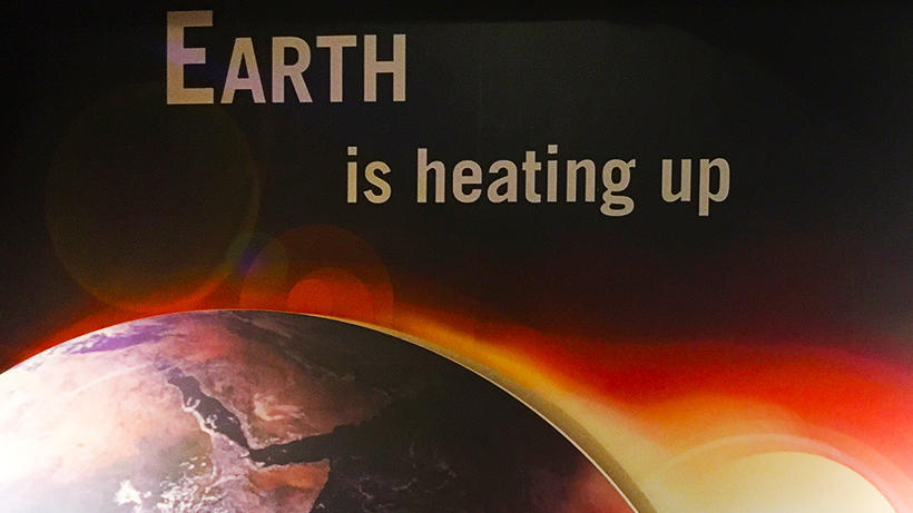 "Picture of Earth near the sun with the text ""Earth is Heating Up"""