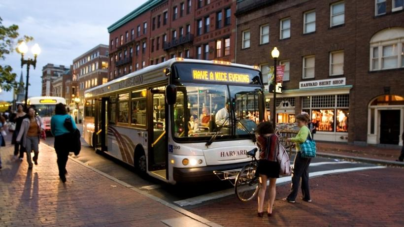 People putting bike on bus in Harvard Square in the evening