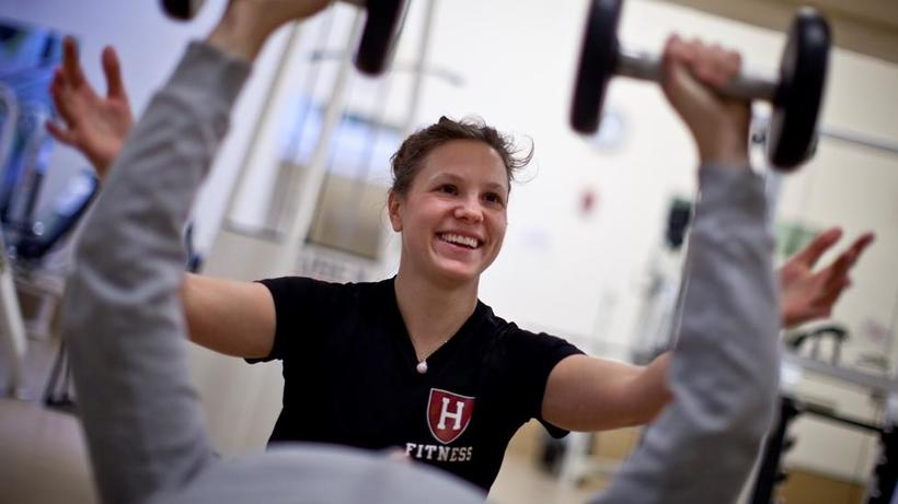 Woman trainer smiling as she helps a client lift weights