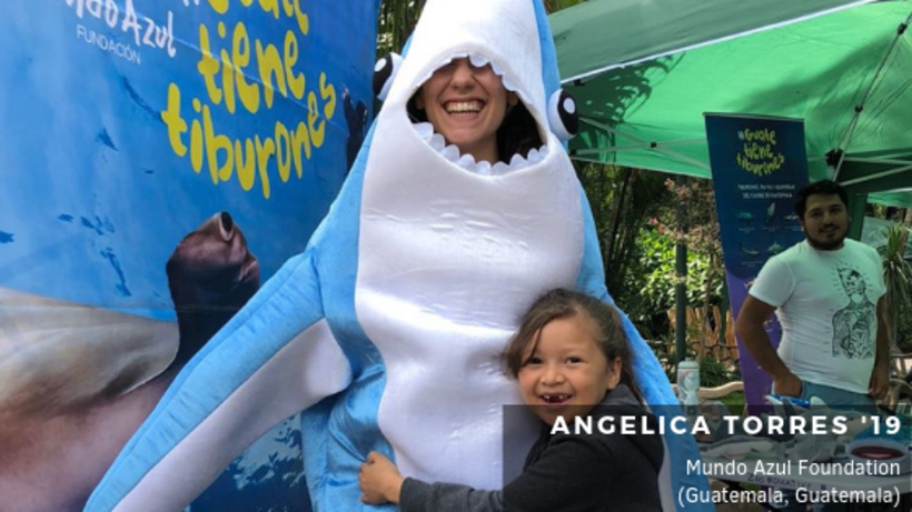 Image of student in shark costume and child hugging