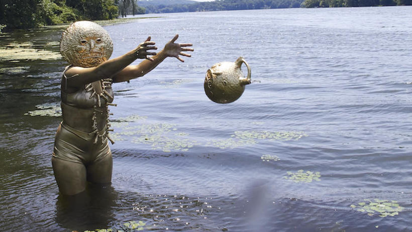 a human figure wearing a gold mask and body paint standing in a lake, surrounded by lilypads, dropping a vessel into the water.
