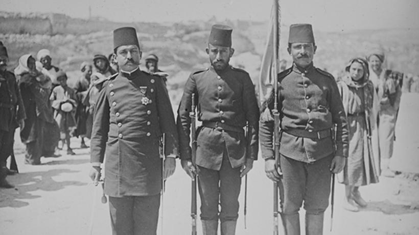 A Turkish officer and two soldiers standing.