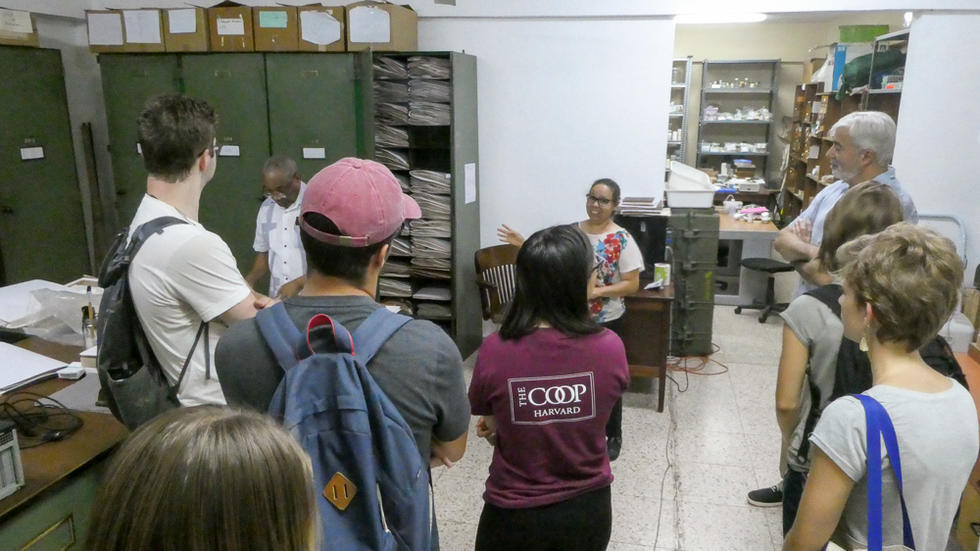 Students and professor listening to member of the Instituto de Investigaciones Botánicas y Zoológicas, surrounded by collections cabinets