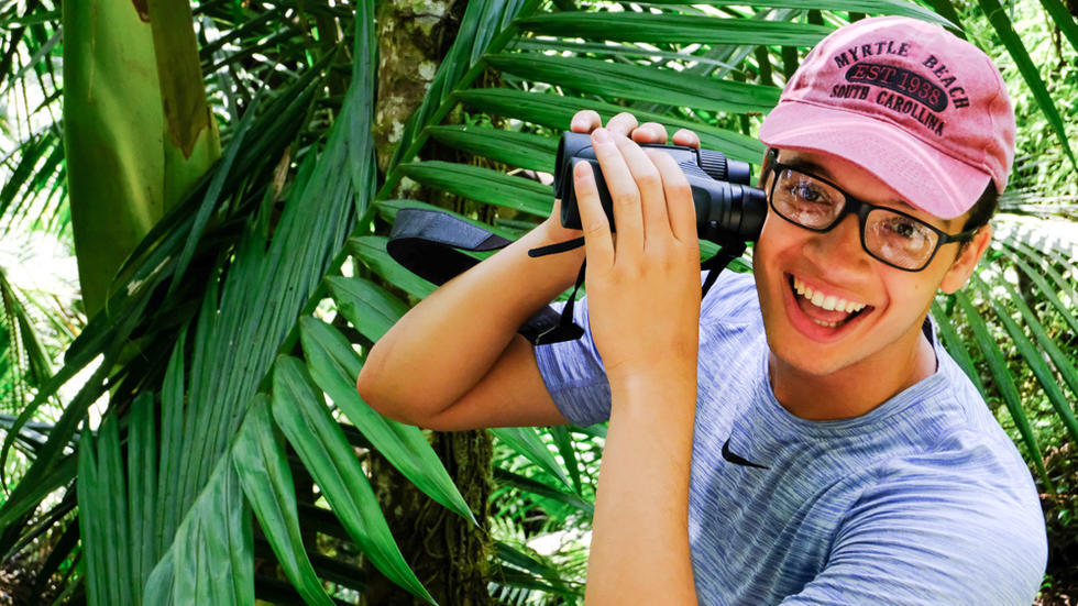 Student wearing baseball cap, smiling, holding binoculars near face. Palm trees in background.
