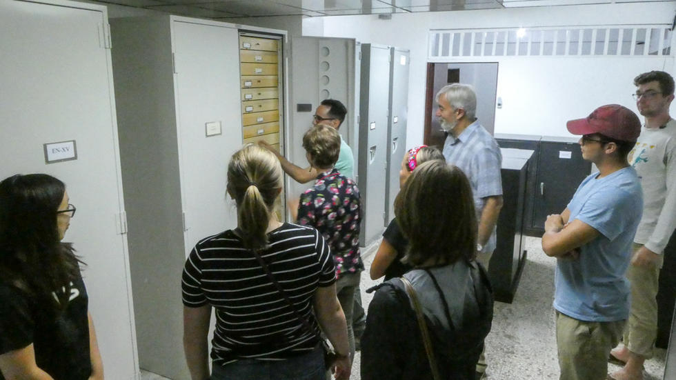 Students and professor being shown natural history cabinets