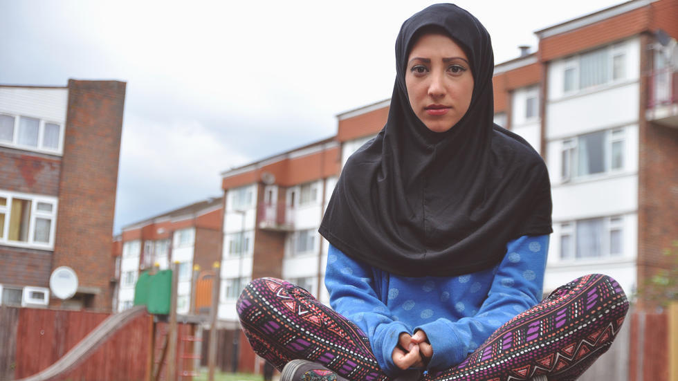 Woman in hijab poses for photo while sitting cross-legged